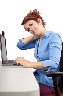 Office worker with a sore neck due to poor ergonomics